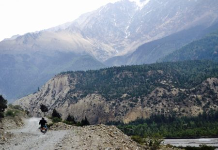 <h3>Riding into Muktinath Valley</h3> From the moment we leave Jomsom, it feels as if we have entered a new world. Now in the subalpine zone (3,000meters +), the peaks of the Dhaulagiri and Nilgiri mountains soar above us. The landscape is rocky and barren with a sharp contrast between the light brownish hue of the terrain and the ethereal vivid blue of the sky. We ride along a stony serpentine road that writhes its way ever deeper and higher into Muktinath valley (3,700meters). Up ahead on the left, we see a village with small green terraced fields. We turn right, on the road that continues climbing towards Jharkot. The Royal Enfield is adept at riding such roads and the sensation of being on the roof of the world is indescribable.